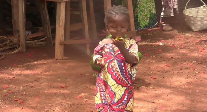 niña come mango poblado Guinea Conakry
